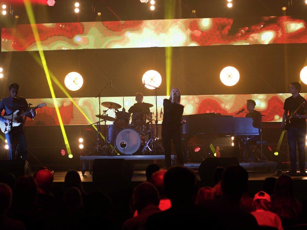 Bilete av bandet Jacob's Dream frå Luster på UKM-festivalen 2018. Fem ungdomar på scenen med gitar, trommer, piano og bass. Proft lysshow. Publikum i salen.