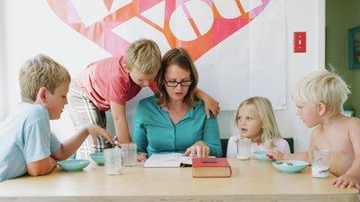 Nainen ja lapset pöydän ääressä