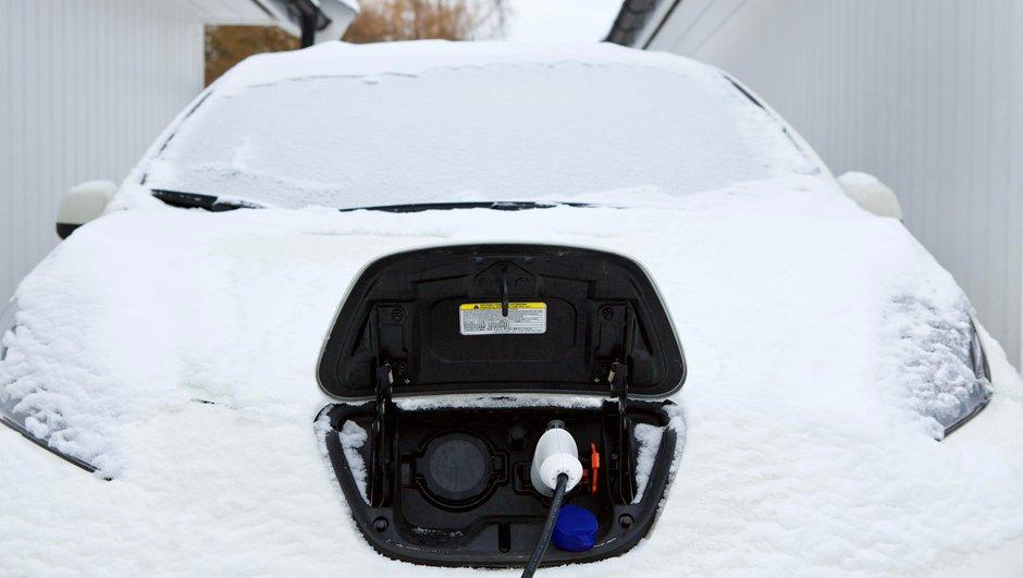 Lumeen peittynyt sähköauto latauksessa.