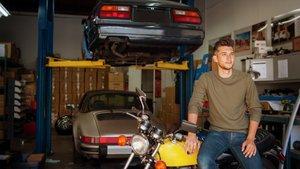 Mies autotallissa usean auton ja moottoripyörän kanssa