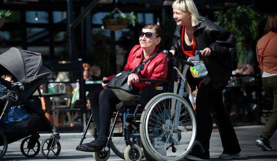 Ragnhild Anita Bjørklund i rullestol trilles av assistent Natalia Balbina forbi fortauskafé