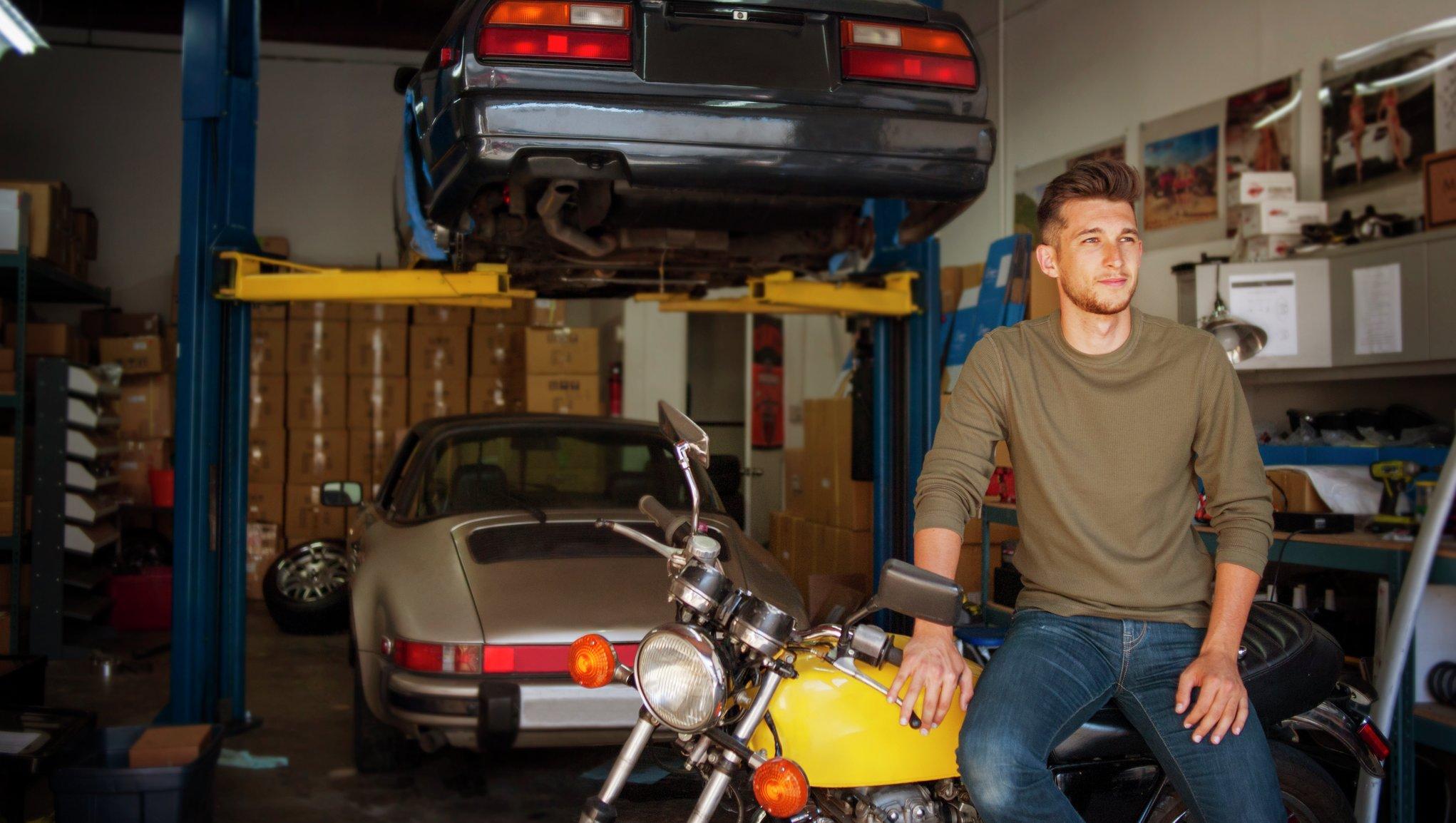 Mies autotallissa kahden auton ja moottoripyörän kanssa
