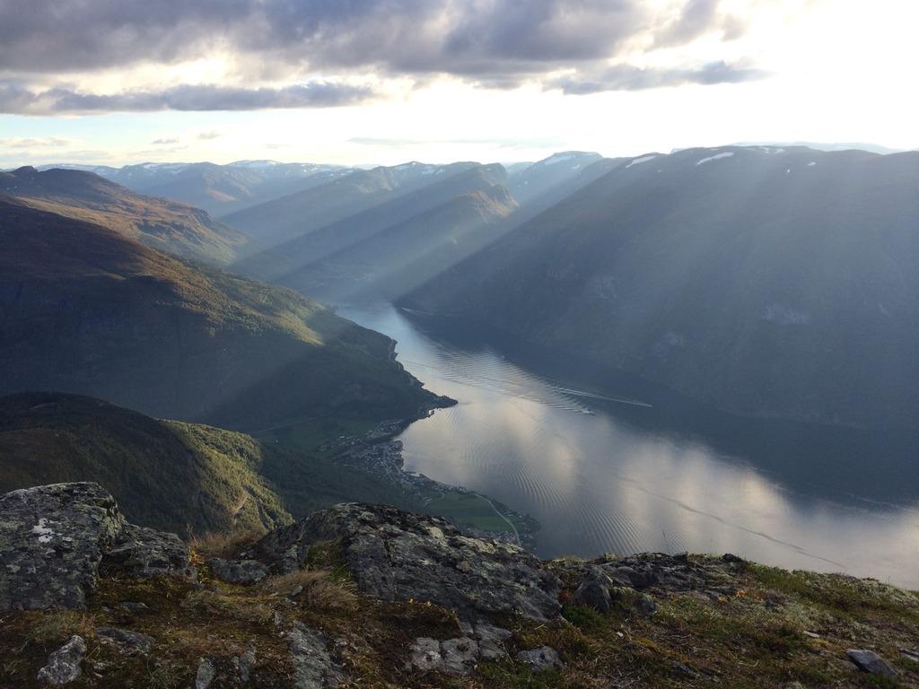 Foto teke frå eit høgt fjell der me får utsikt nedover mot Aurlandsfjorden og Aurlandsvangen. Sola bryt seg gjennom skylaget og sendet solstrålar nedover mot fjellet.