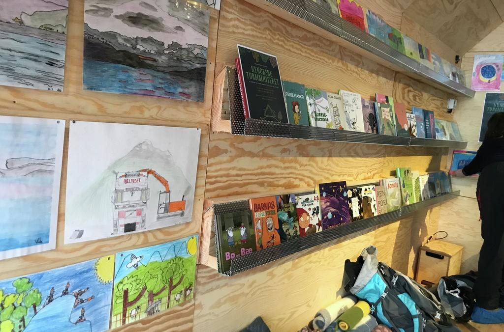 Foto frå inni dagsturhytta på Sandane. Vi ser både det nynorske turbiblioteket og kunstutstillinga elevar ved Nordstranda skule hadde laga til opninga.