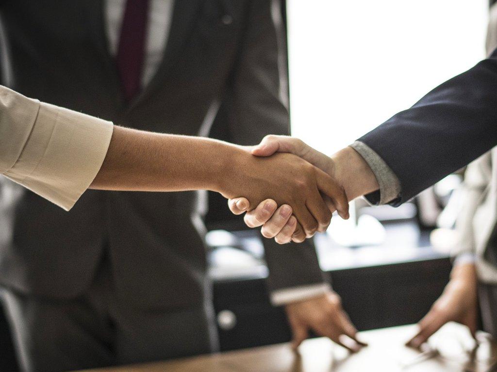 To personar tek kvarandre i hendene i eit kontorlokale.