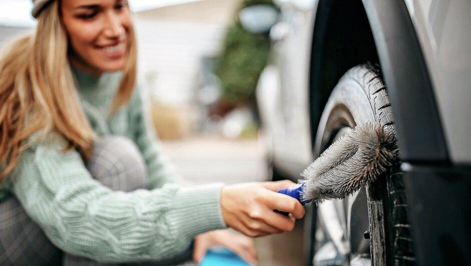 kvinna rengör däck på bil