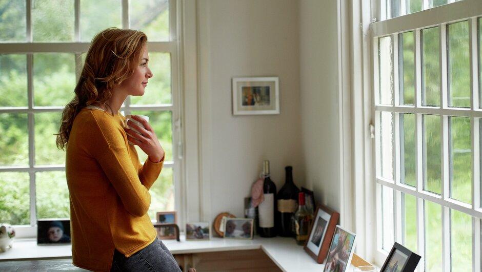 Kvinna håller koll på grannes hus