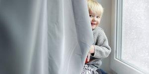 barn gömmer sig bakom gardin
