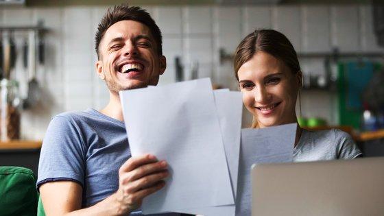 Nainen ja mies katsovat papereita ja tietokonetta