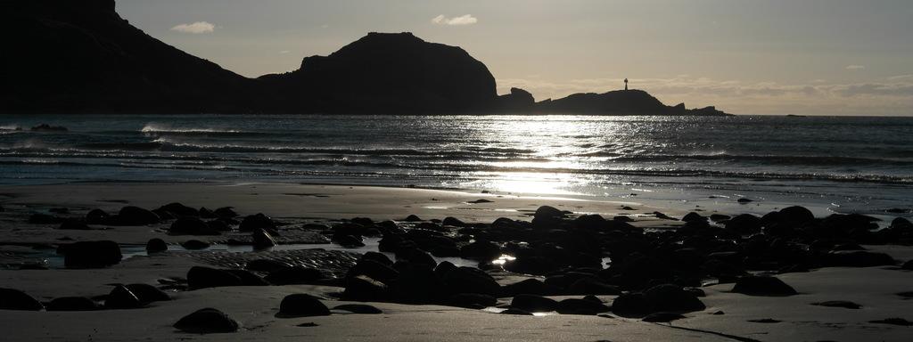 Foto som syner ei sandstrond i motlys. Sola er på veg ned, men har framleis eit stykke att før ho treff havet.