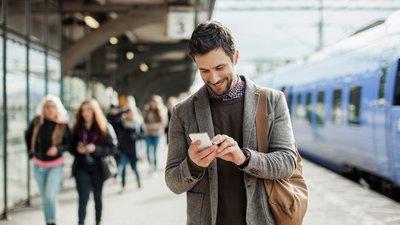 Mies juna-asemalla puhelimen kanssa