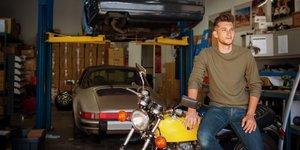 En man i garaget med motorcykel och bilar