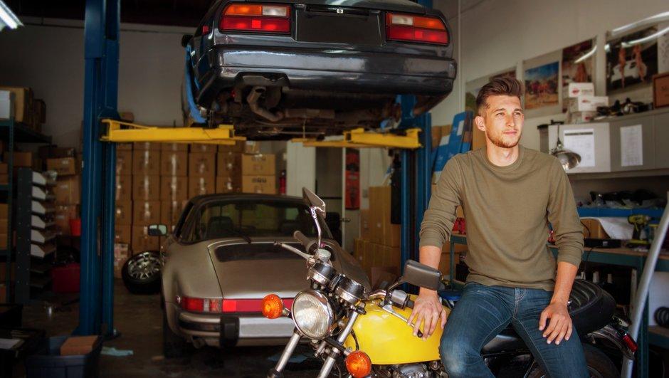 En ung man i garaget med bilar och en motorcykel.