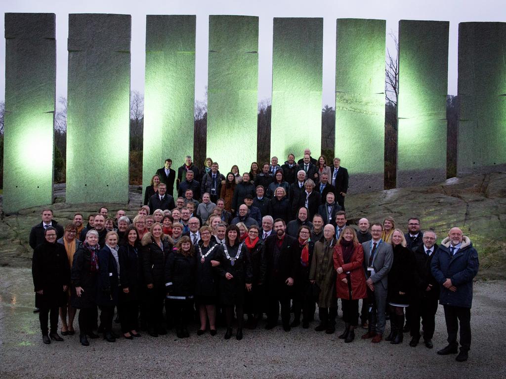 Foto av fylkestinga i Sogn og Fjordane og Hordaland samla framfor tingveggen på tingstaden Gulatinget i Gulen. Steinhellene i bakgrunnen er lyste opp med grønt lys.