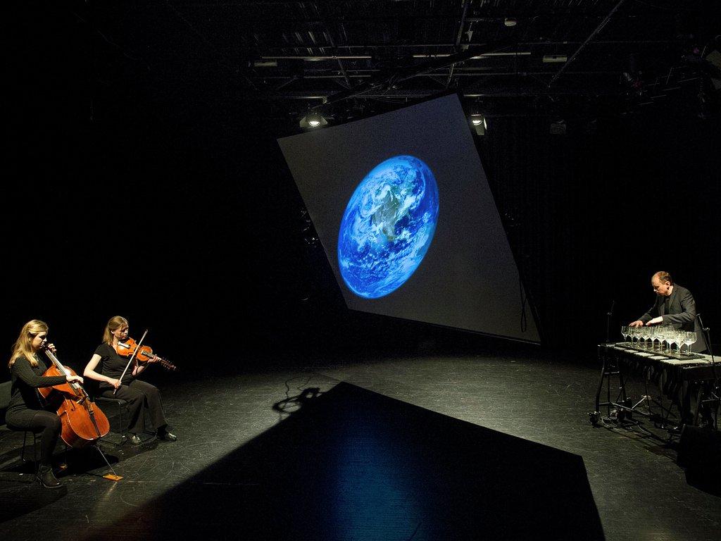 Bilete frå framsyning. To kvinner sit og speler fiolin og cello, ein mann  står og speler på glas. Mellom dei heng ein jordklode.