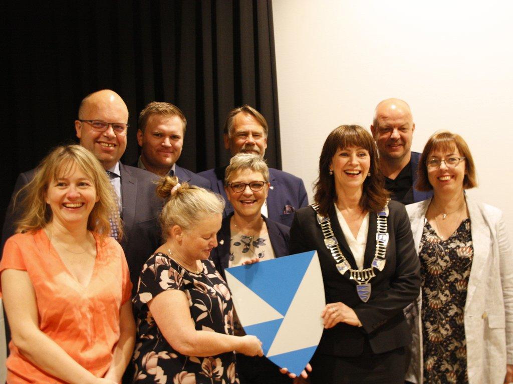eit samla fylkesutval står inne i eit møterom og held fram det nye fylkesvåpenet for Vestland fylkeskommune, alle smiler.
