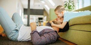 Man och pojke leker i soffan