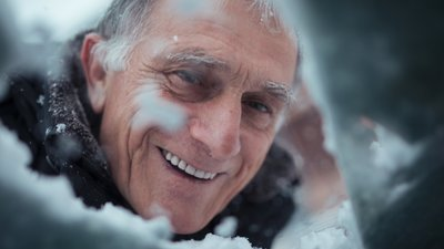 Mies lakaisee lunta auton tuulilasista