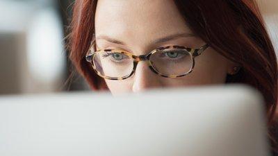 Silmäläsipäinen nainen tuijottaa tietokonetta