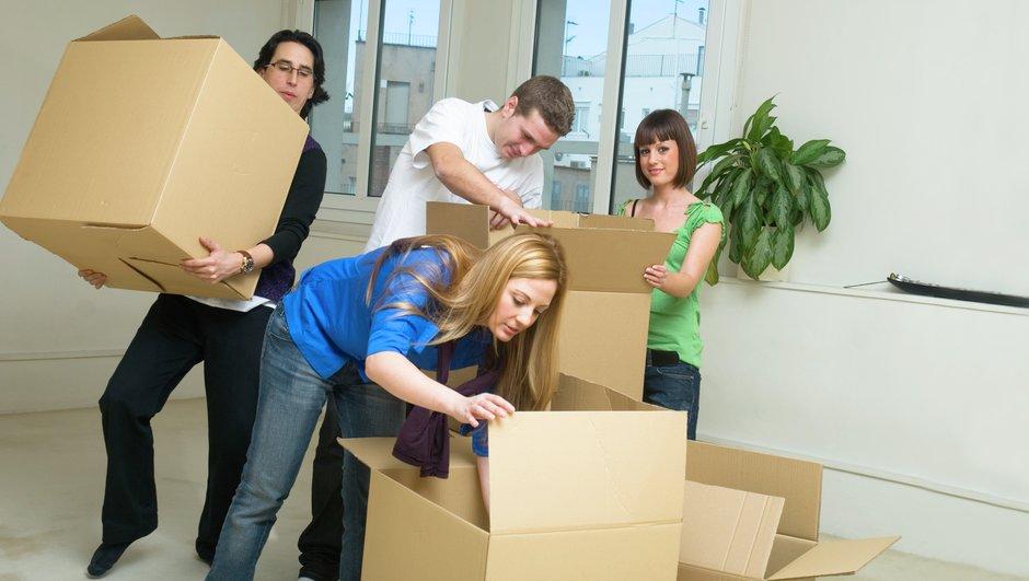 Unge mennesker der flytter papkasser.