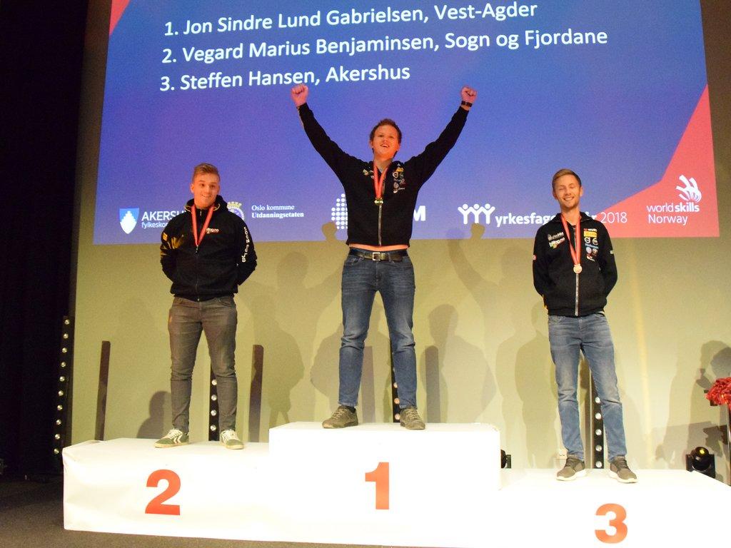 Tre bilfaglærlingar på pallen under medaljeseremonien på yrkes-NM med medalje rundt halsen.