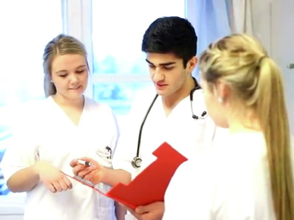 Foto av tre praksiselevar, to jenter og ein gut, i doktor-/sjukepleiaruniform. Dei står og ser i ei raud mappe.