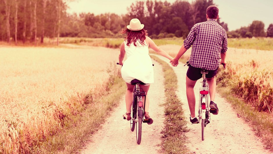 Mand og kvinde cykler på hver deres cykel og holder hinanden i hånden.