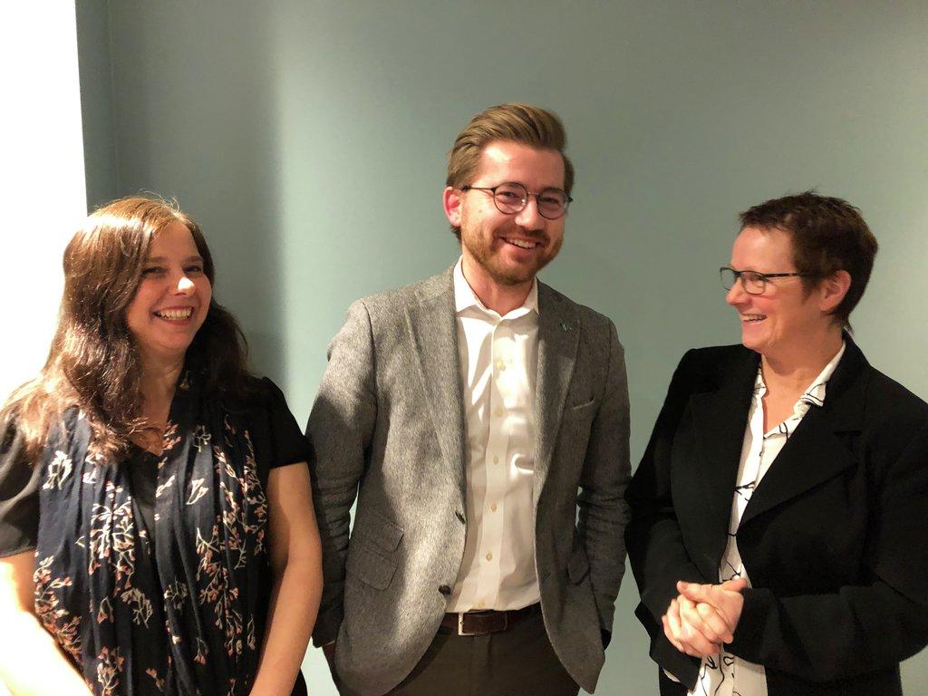Arlen Bidne, Sveinung Rotevatn og Karen Marie Hjelmeseter står oppstilt ved ein vegg og smiler.