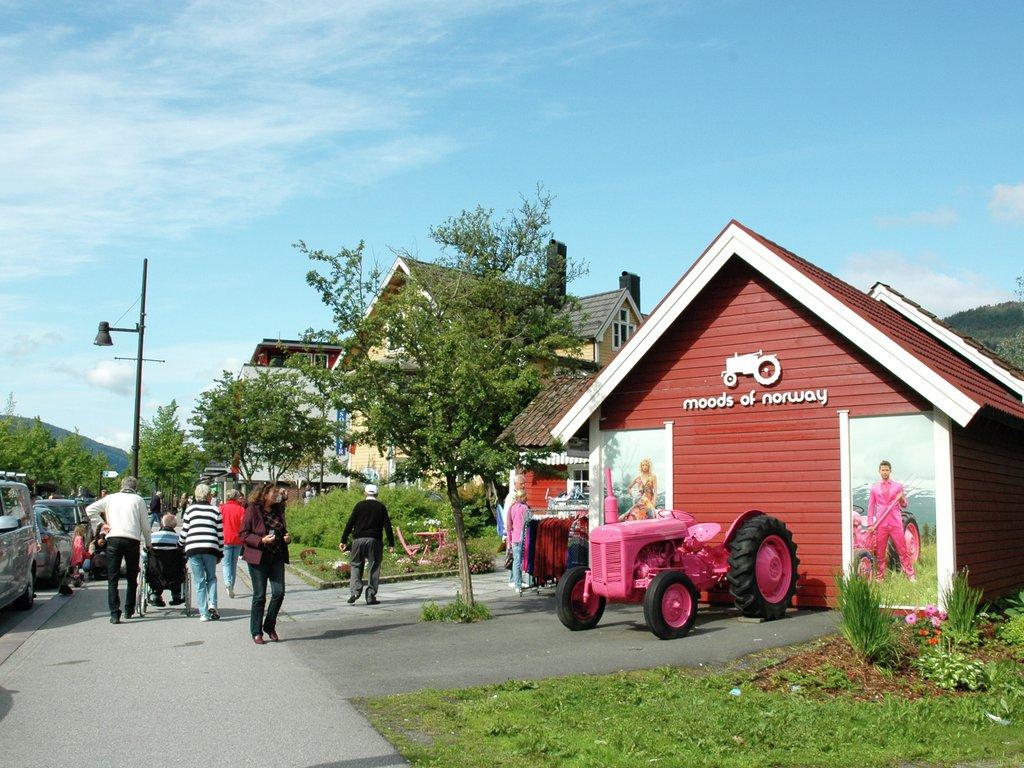 Foto frå Tonningsgata i Stryn ein sommardag. Det er folk på fortauet, og bilar står parkerte. Til høgre i biletet er det vesle, raude huset med utsalet til Moods of Norway, med den rosa traktoren utanfor.