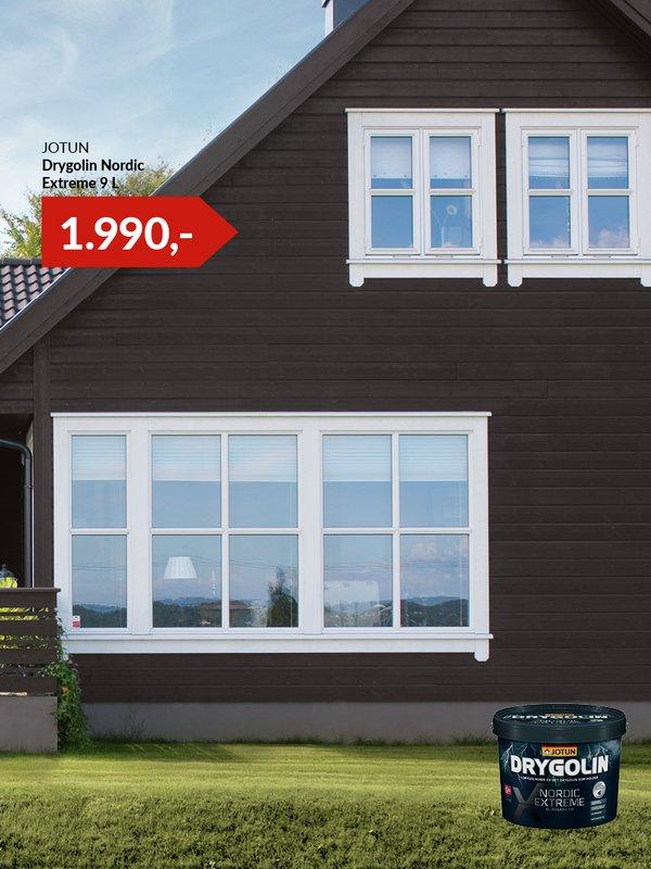 Sort husfasade i moderne hyttestil med mange vinduer og terrasse med rekkeverk på grønn plen