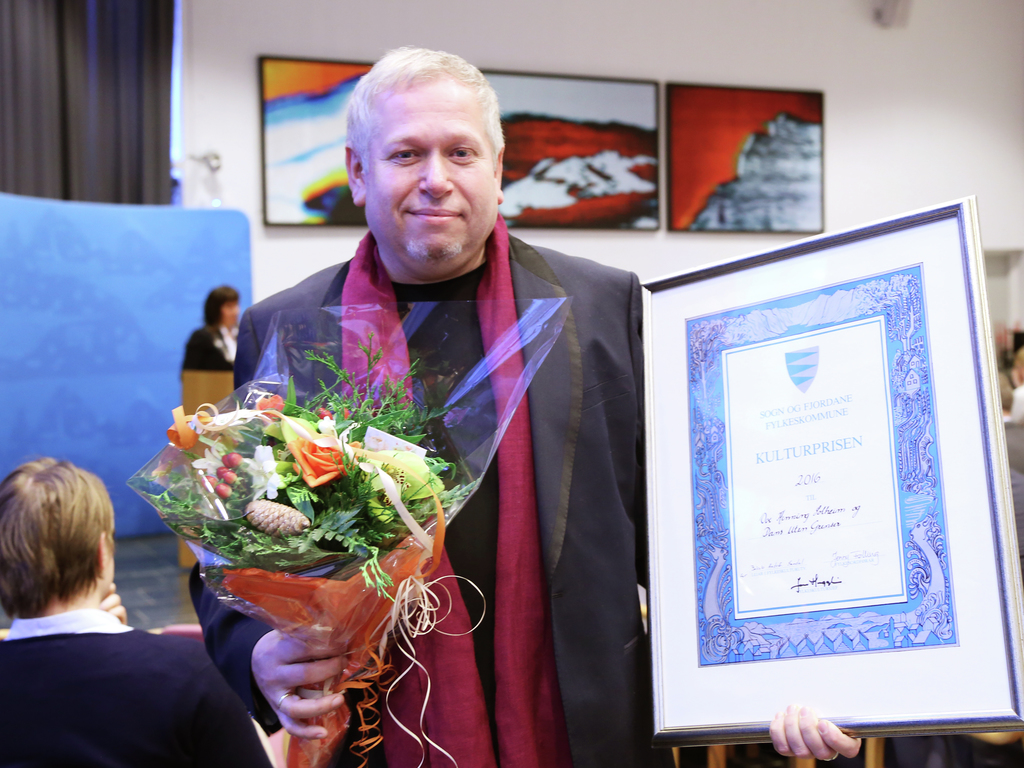 Foto av Ove Henning Solheim som nettopp har teke imot fylkeskulturprisen 2017. Han held diplomet og ein blomsterbukett i handa, og i bakgrunnen ser vi fylkestinget.
