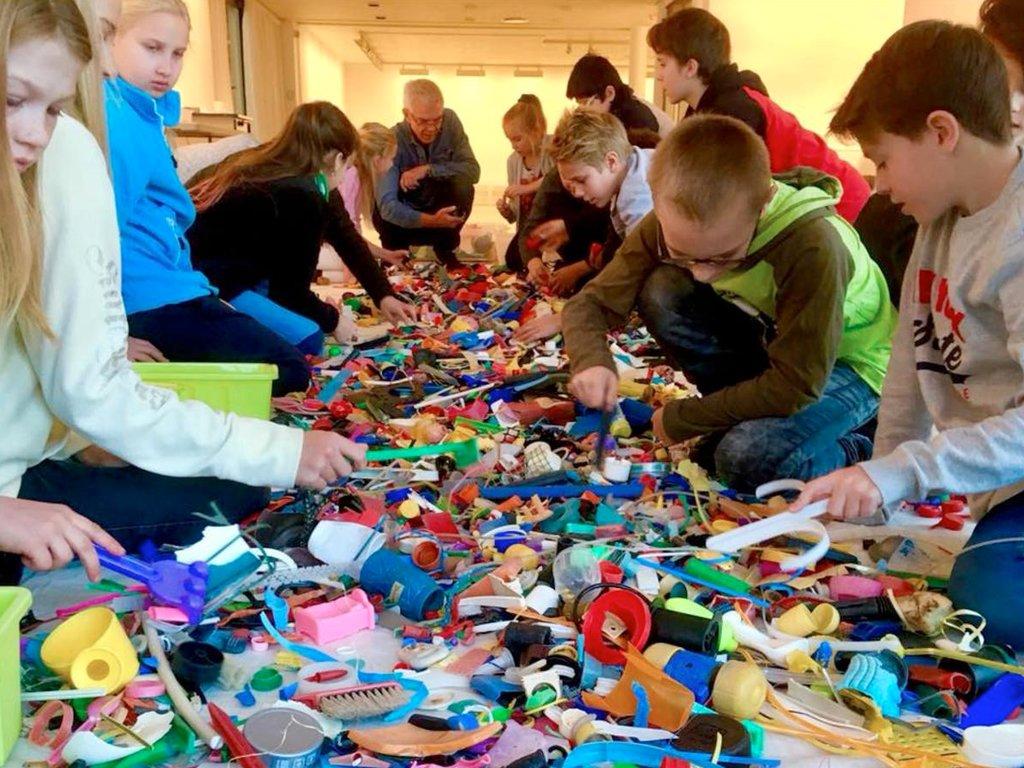 Frå produksjonen Verken fugl eller fisk – i eit hav av plast, Den kulturelle skulesekken. Vi ser skuleborn som leitar i plastbitar på eit bord.