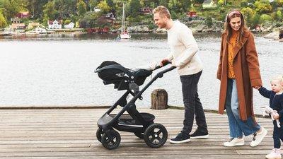 Mies työntää lastenvaunuja vierellään nainen ja lapsi