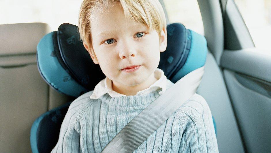 Pojke sitter på bälteskudde