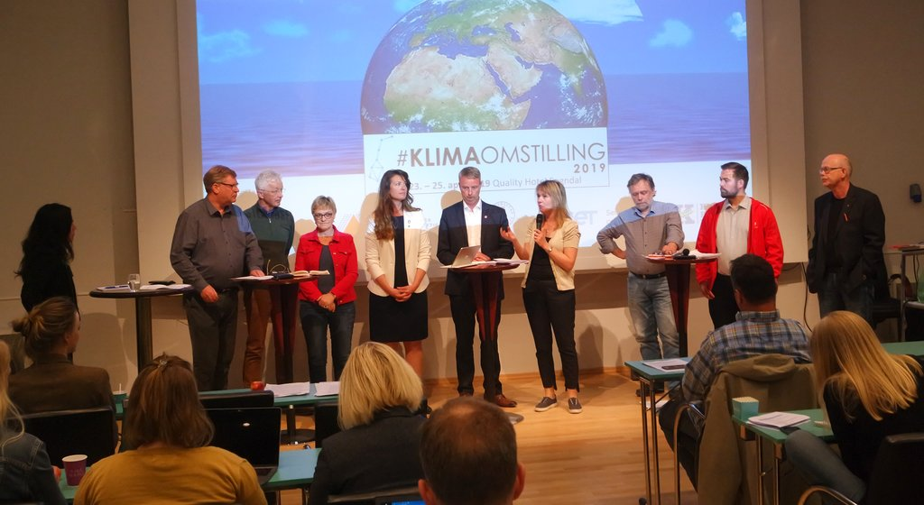 Valkampdebatt under klimaomstillingskonferansen i Sogndal i april 2019, ni politikarar står på rekkje i ein stor møtesal